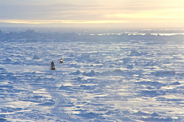 Photo of two community members returning by snowmobile